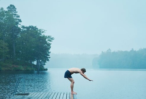 Photo of a man diving into a lake.
