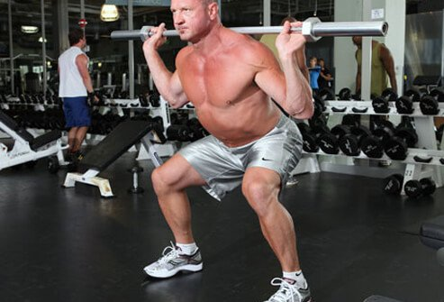 Photo of a man doing squats with a barbell.