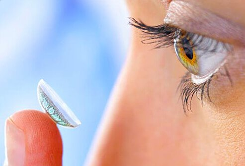 Photo of woman applying contact lens.
