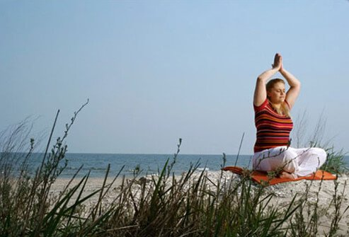 Photo of a woman doing yoga on the beach, reducing stress.