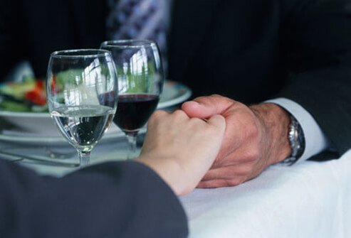 Photo of couple holding hands at dinner.