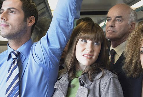 Woman on crowded commuter train.
