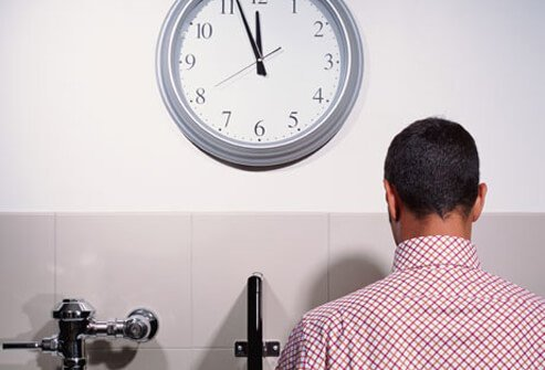A man at the urinal by a clock.
