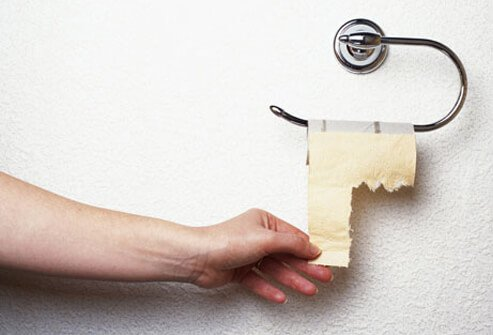 Photo of hand reaching for toilet paper.
