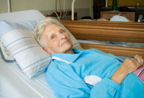Elderly woman lying in a nursing home bed.