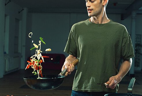 A man flipping vegetables in a wok.